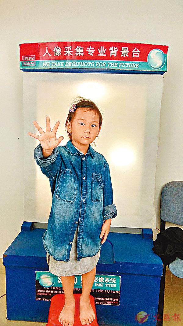 ■ 翁偉書家裡最小的孩子翁茉文在採集照片時,請民警阿姨給她拍得漂亮點。香港文匯報記者蔣煌基 攝