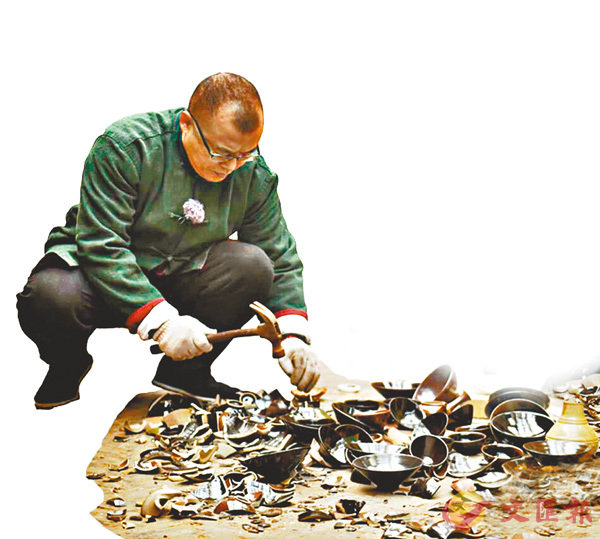 ■精品難求,伍映山在反覆嘗試燒製的過程中,估計敲碎數以萬計的次品。圖為伍映山在砸有殘缺的瓷器。 香港文匯報江西傳真