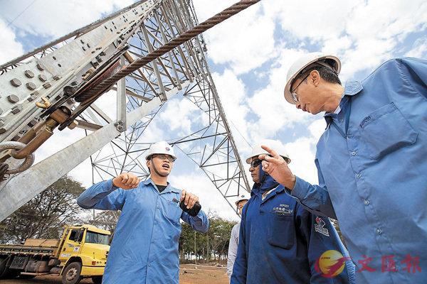 ■中國企業對「一帶一路」沿線國家投資合作積極推進。圖為巴西美麗山特高壓輸電工程二期第九標段項目中方現場施工管理負責人指導巴方員工。 新華社