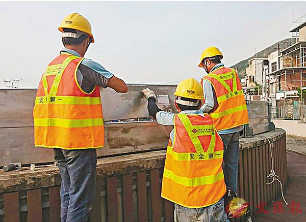 ■渠務署人員在大澳加裝擋水板防海水倒灌。 香港文匯報記者顏晉傑  攝