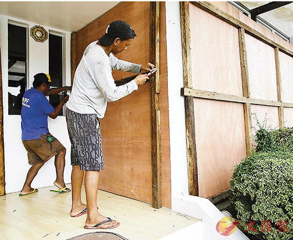 ■居民釘上木板,以防家園受損。 美聯社
