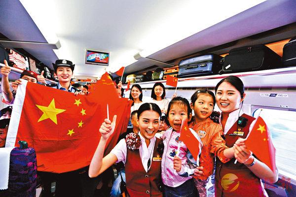 ■昨日是十一黃金周首日,內地搭高鐵赴港旅客全天逾6萬人。圖為昨日福州開往西九龍的列車上,「高姐」與乘客一起慶祝國慶。 中新社