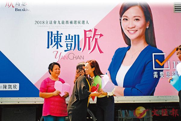 ■昨日宣佈參加九龍西補選的陳凱欣接受支持者擁抱,義工華姐手持一顆「心」站台打氣。香港文匯報記者梁祖彝  攝