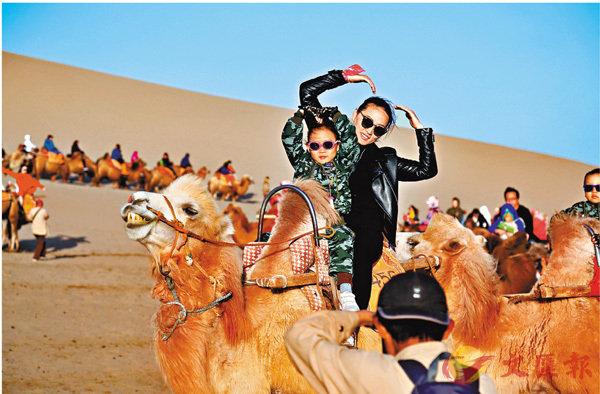 ■動車帶動「絲路」旅遊熱。圖為遊客在甘肅敦煌鳴沙山騎駱駝。 新華社