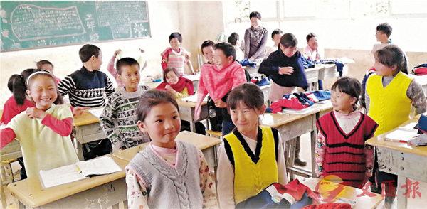 ■收到毛衣的孩子笑得很開心。  香港文匯報雲南傳真