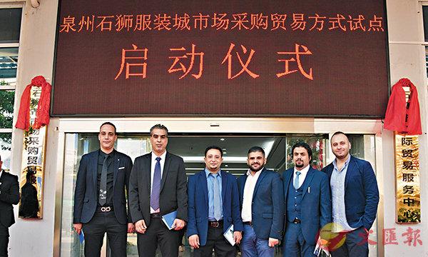 ■參加「石獅服裝城國家市場採購貿易試點」啟動儀式的外商在現場合影,為中國越來越便利的通關政策點讚。記者蔣煌基 攝