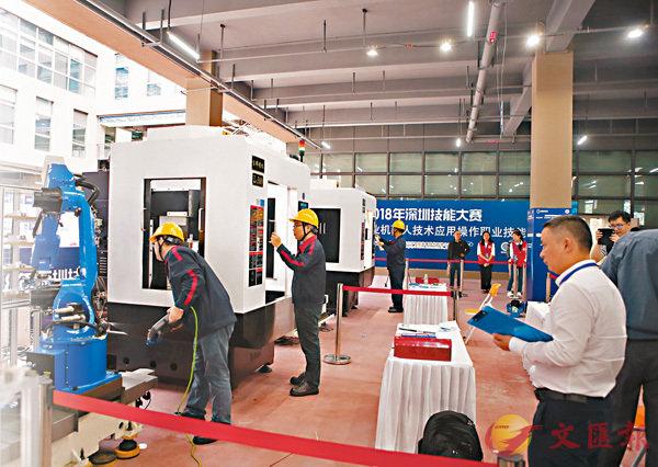 ■工業機器人競賽吸引了許多企業和學校選手參賽。圖為技術工人在調試機器人準備競賽情況。