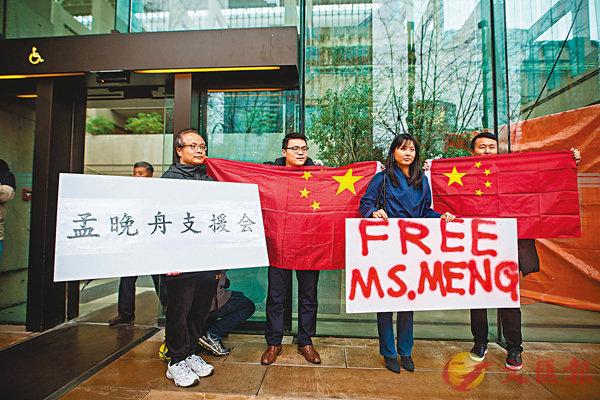 ■ 支持者手持「釋放孟(晚舟)女士」的標語和中國國旗在法院外聲援。 彭博社