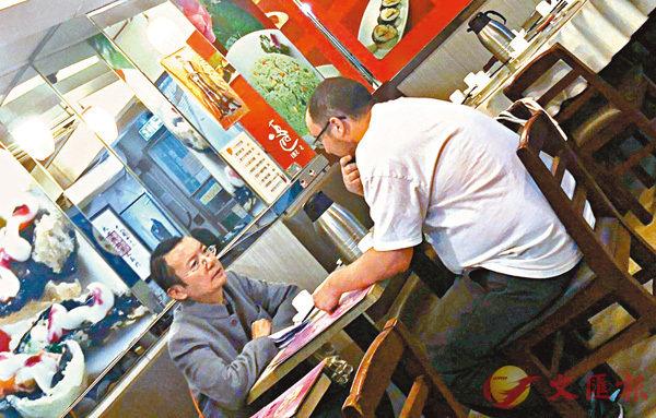 ■12月11日下午,凱大熊(白衫)在旺角一家素食餐廳與「本土新聞」創辦人曾焯文密斟。 香港文匯報記者張得民  攝
