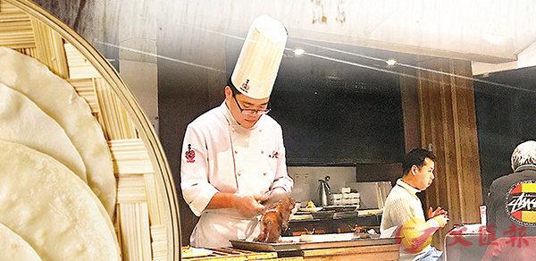 ■ 北京烹飪協會日前發佈了北京烤鴨技術規範。圖為廚師給顧客片北京烤鴨。香港文匯報記者張聰 攝