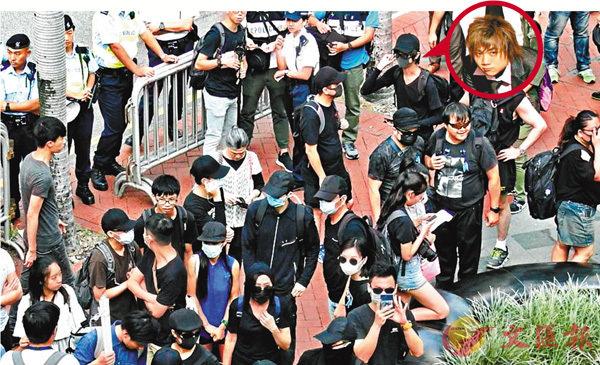 ■2018年10月1日,一批穿黑衣的「獨派」組織成員聚集在灣仔修頓球場準備參與遊行。阿湯(圓圖)戴�茤蛣P黑口罩在黑衣人的外圍。 資料圖片