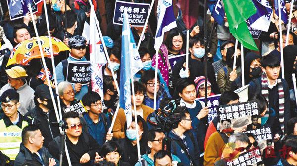 ■多個「獨派」組織元旦參與反對派的遊行活動。圈中人由左至右,鄭俠、鍾翰林、陳家駒、梁頌恆舉�荂u獨旗」、「獨幡」出現在遊行隊伍中。 香港文匯報記者張得民 攝