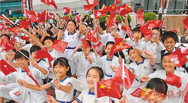 ■中小學將須教授唱國歌。圖為學生們在活動上揮動國旗和區旗。 資料圖片