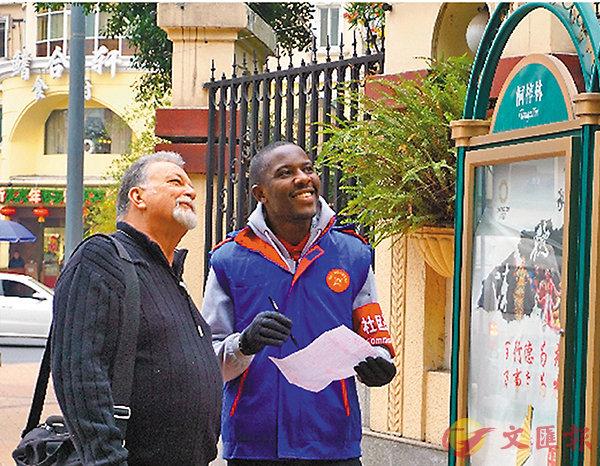 ■約翰(左)與桐梓林社區的外籍人士巡邏隊員在街上工作。 網上圖片
