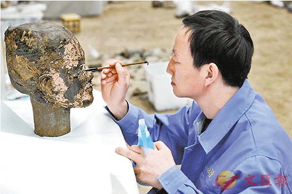 ■ 文物保護專家正在處理兵馬俑面部彩繪。香港文匯報陝西傳真