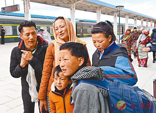 ■旅客格桑德青(左一)和家人抵達海拔4,700米的安多火車站。 新華社