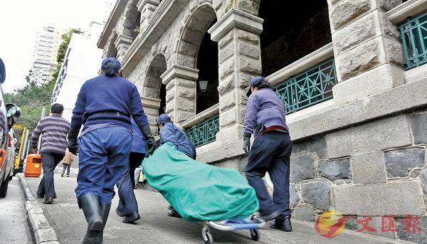 ■猝死梯間保安員遺體由仵工舁走。