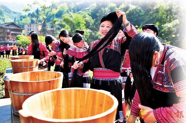 ■ 在近日廣西龍勝黃洛紅瑤寨的長髮節上,瑤族女子在��外展示長髮梳妝。 新華社