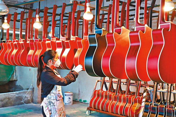 ■中央強調落實好中央經濟工作會議精神。圖為4月10日在由貧困縣變為「中國吉他製造之鄉」的貴州省遵義市正安縣,一名工人正在整理噴漆後的吉他。 中新社