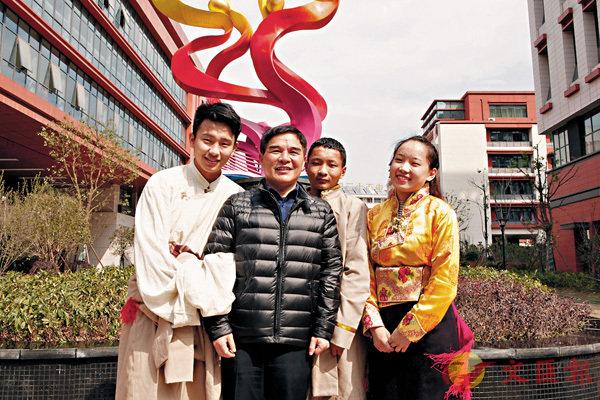 ■范德標(左二)與藏族學生次仁朗傑(左一)、白瑪頓珠(右二)、益西措姆(右一)在學校彩色哈達建築前留念。 香港文匯報記者趙臣  攝