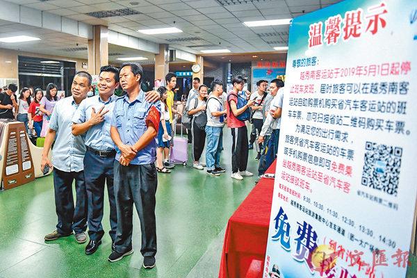 ■ 4月30日晚,越秀南客運站員工在最後一班客車的旅客隊伍前合影。 中新社