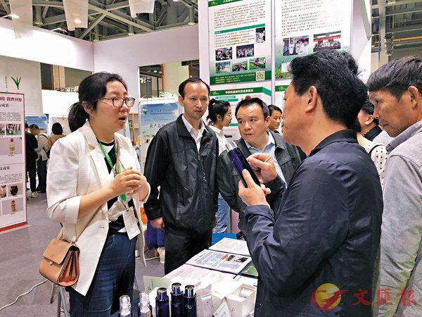 ■茶博會上參觀者饒有興趣向開發者了解茶化妝品的功效。香港文匯報記者王莉  攝