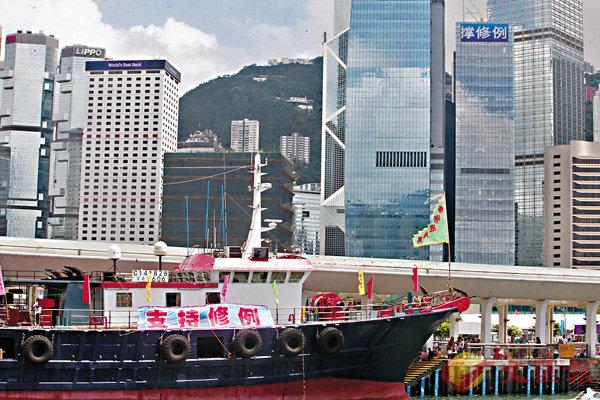 ■漁船巡遊撐修例和大廈頂上的廣告互相呼應。 香港文匯報記者莫雪芝 攝