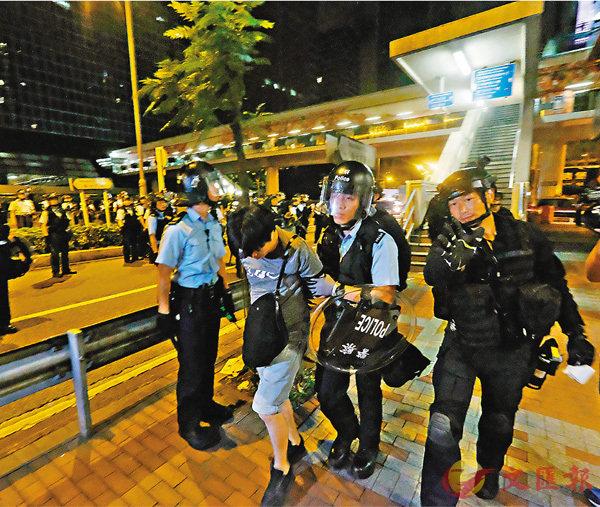 ■上周日晚有暴力分子衝擊立法會,大批警員出動維持秩序,其間有衝擊者被警方帶走調查。 香港文匯報記者梁祖彝  攝