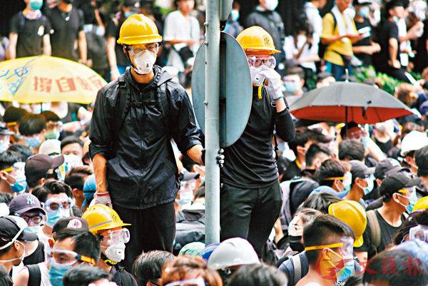 ■多名全身包實的「蒙面人」發號施令。香港文匯報記者梁祖彝  攝