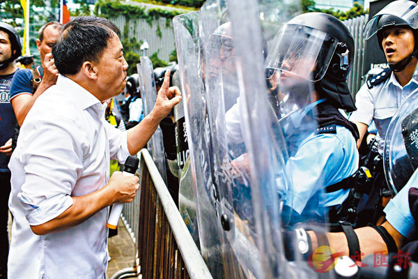 ■胡志偉在警方防線前「擺拍」,其後不見蹤影。 資料圖片