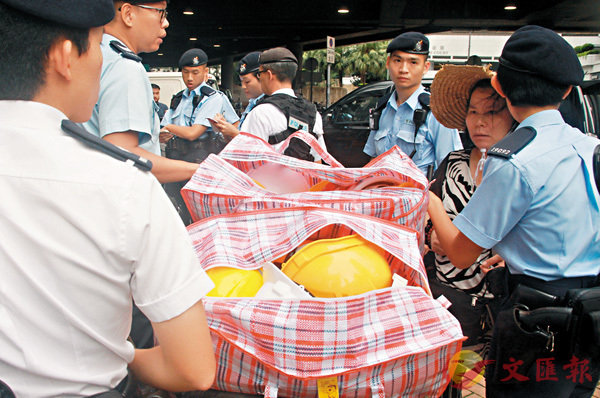 ■警員截獲大批簇新的頭盔,一名中年女子報稱是自己拾荒得來。 香港文匯報記者鍾立  攝