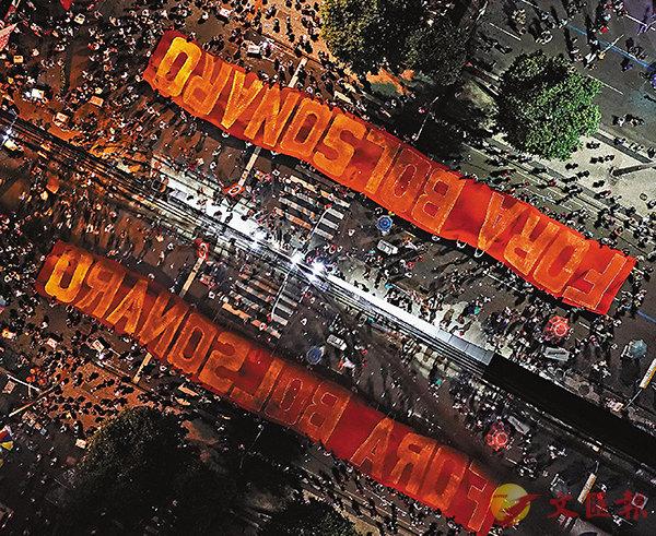 ■示威者展示印有「博爾索納羅下台」的橫額。  美聯社