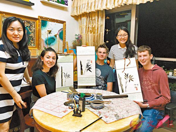 ■倩瑩(右二)及她的媽媽(左一)招待外國交流同學在家學水墨畫。 科大供圖