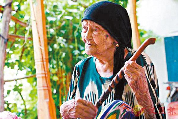 ■ 世界上最長壽者阿麗米罕·色依提25日在家中迎來133歲生日。圖為阿麗米罕將枴杖當樂器彈奏,邊唱起了歌。 網上圖片