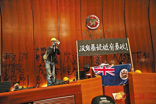 ■示威者在立法會主席台上擺上了標語和港英旗幟,並塗污背景牆。 香港文匯報記者 攝