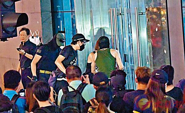 ■6月26日,楊逸朗(綠背心者)與3名激進示威者在警總玻璃門外準備衝擊,而旁邊的立法會議員郭家麒視而不見。 資料圖片