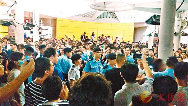 ■港鐵油塘站前晚聚集逾百名青年叫囂,警方一度高舉紅旗警告。 香港文匯報記者  攝