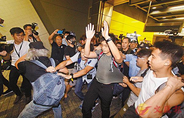 ■ 灰衣男子被多名男女包圍,便衣警將雙方分隔。 香港文匯報記者  攝