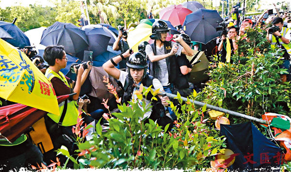 ■本月13日,「光復上水」遊行引發暴力衝擊。圖為警員被暴徒的鐵支雨傘包圍。 資料圖片