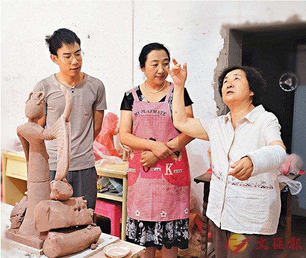 ■王蒨(右一)向學生模擬陶俑風姿,希望將陶俑複製得更有神韻。 香港文匯報記者張仕珍  攝