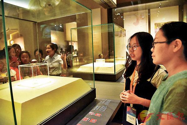 ■陝西歷史博物館香港大學生志願者講解員薛恩如(左)向遊客講解「獨孤信印」。