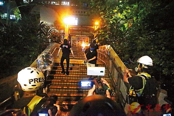 ■ 暴徒在尖沙咀警署鐵門外縱火。香港文匯報記者  攝
