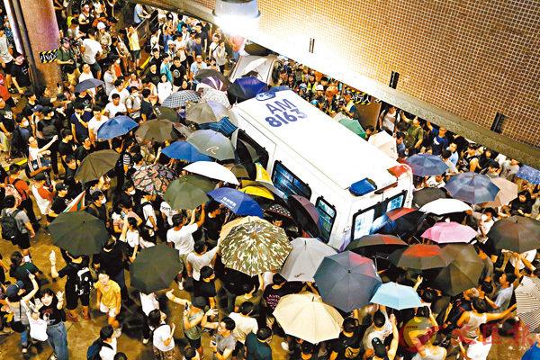 ■大批示威者在黃大仙港鐵站外包圍警車並阻止警車離開。香港文匯報記者  攝