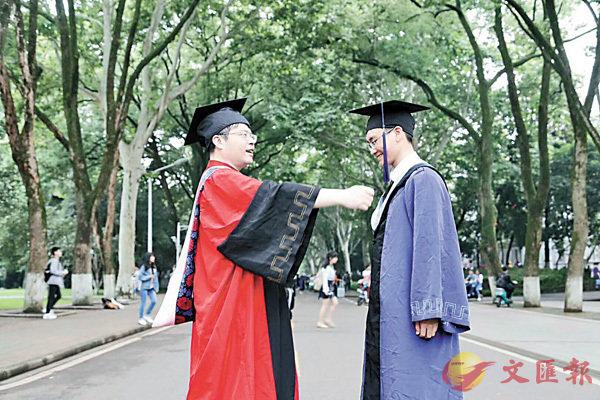 ■龔勝生(左)為畢業的研究生撥穗。  受訪者供圖