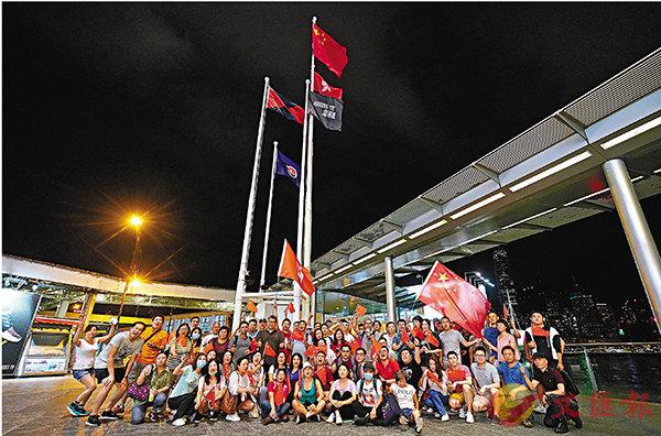 ■8月5日晚11時左右,香港市民自發到尖沙咀天星碼頭附近的升旗台升起五星紅旗。 中通社