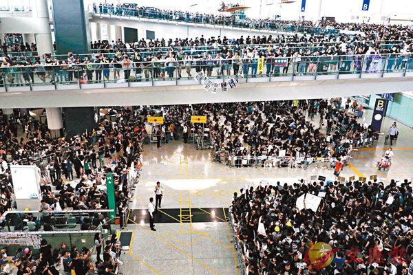 ■黑衣人在機場出入境大堂非法集結。 香港文匯報記者 攝
