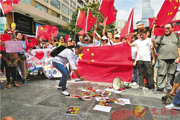 ■市民團體「同心護港」昨日在尖沙咀五支旗杆下舉行護國旗活動,他們將四處禍港的暴徒比喻為一群��禲A並噴殺蟲劑以示為港「滅蟲」的決心。香港文匯報記者  攝