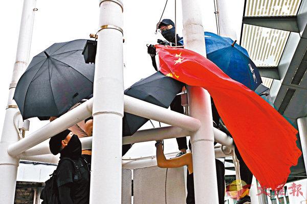 ■暴徒在同黨協助下,把尖沙咀「五支旗杆」上的國旗取下並拋進海中。 資料圖片