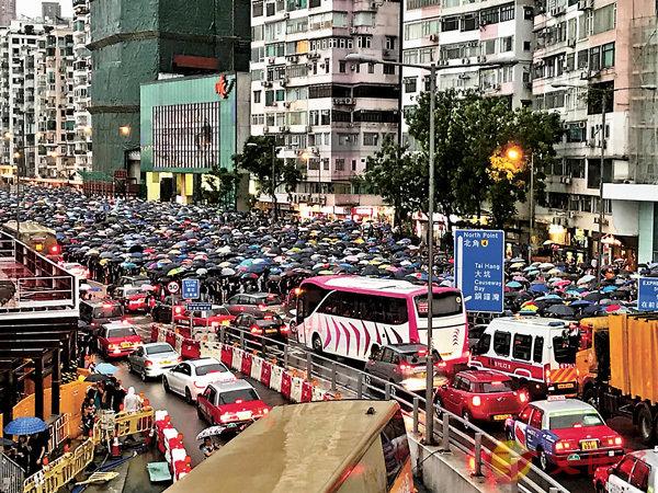 ■ 民陣舉行「流水式」集會,後因現場人數眾多演變成「遊行」,令港島重要幹道交通癱瘓。 中央社