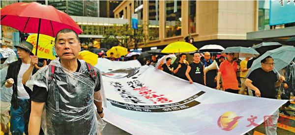 ■黎智英、李柱銘、何俊仁等昨日帶頭拉起直幡,步出維園煽動非法遊行。 中央社